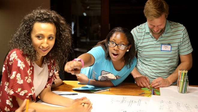 LARRY STEAGALL | KITSAP SUN Destyni Hollie, 11, of Bremerton, points to a team member during 'STEM for OurGEMS' at Rice Fergus Miller architects in Bremerton. On the left is Shianne Davis, 14, of Poulsbo, working with architect Dean Kelly, right.