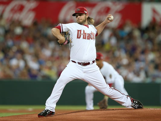 The Diamondbacks' Wade Miley throws the first pitch from the opening game of the 2014 Major League Baseball season between the Los Angeles Dodgers and Arizona Diamondbacks at the Sydney Cricket ground in Sydney, Saturday, March 22, 2014.  (AP Photo/Rick Rycroft)