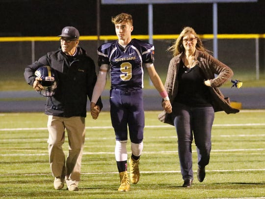 Gary Raupers walks onto the field with his dad, Gary Raupers Sr., and his mom, Wendi Raupers, during Senior Night for football Oct. 13 at Brewer Memorial Stadium.