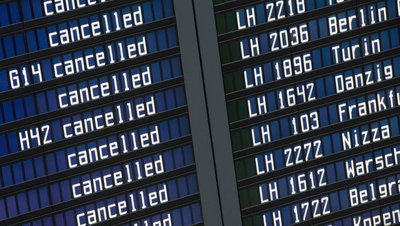 A departure board shows many canceled flights at the