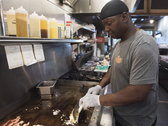 Ed Dixon mans the grill at Hot Dog Deli on Friday, Sept. 1, 2017. The grill and fry station were added after a recent remodel.