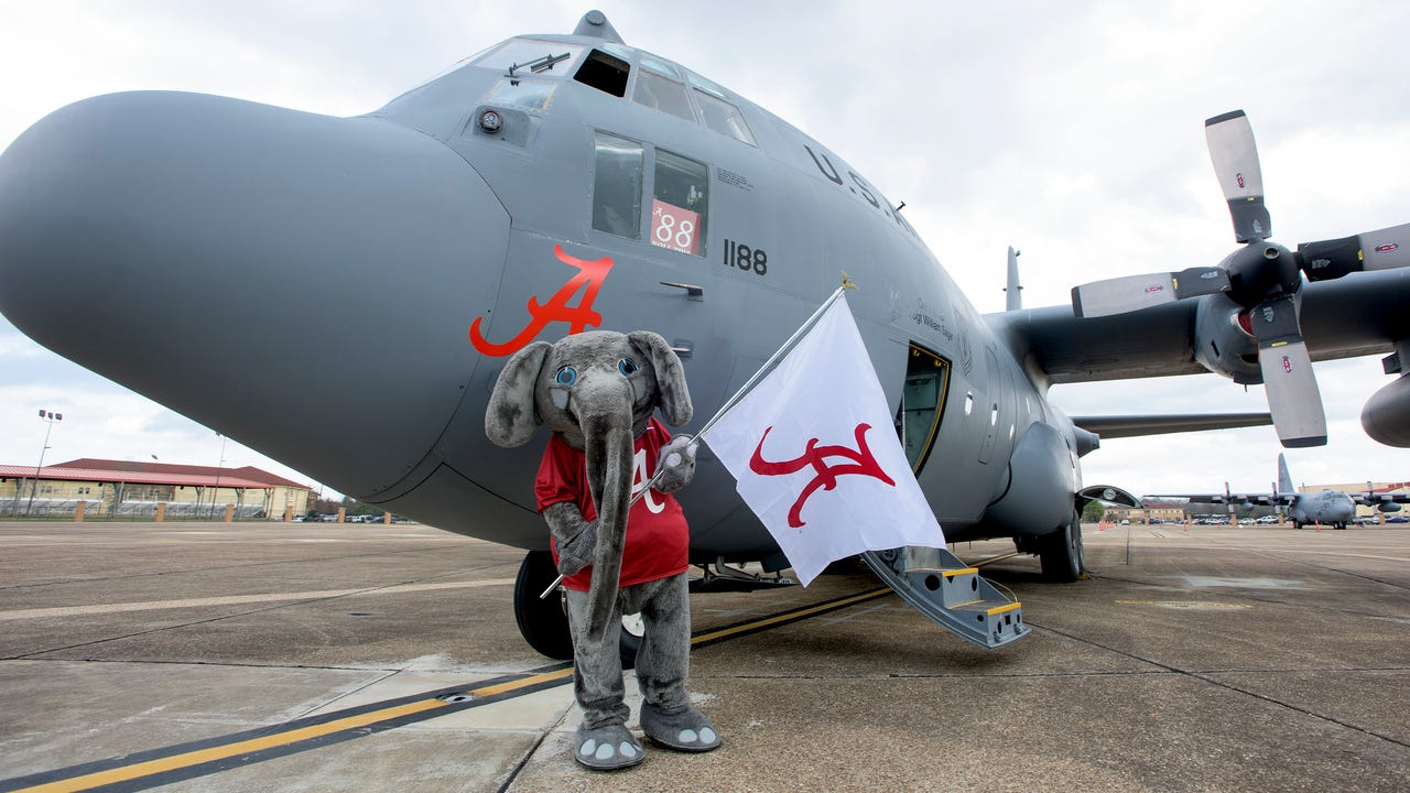 Alabama mascot Big Al carries a flag from the the old plane to the new one during the retirement of the C-130, Roll Tide, at the 908th Airlift Wing at Maxwell AFB in Montgomery, Ala., on Friday January 20, 2017. (Mickey Welsh / Montgomery Advertiser)
