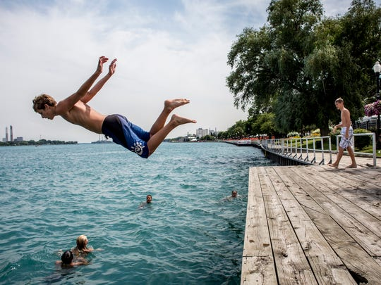 Aiden Gaedcke, 13, of St. Clair, runs and leaps into the St. Clair River Thursday, July 28, 2016 while swimming with friends in St. Clair.