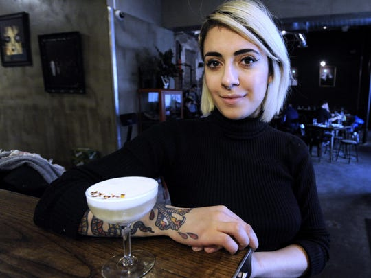 Rock City Eatery beverage director Anna Atanassova, 23, of Detroit, poses with a warm mescal and coconut milk cocktail at the restaurant.