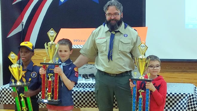 From left to right: Fashion Smith, Jake Burton, den leader Jarrod Moreau and Logan Schwab celebrate placing in the top-three at Saturday's District Pinewood Derby competition at Hermosa Elementary in Artesia.