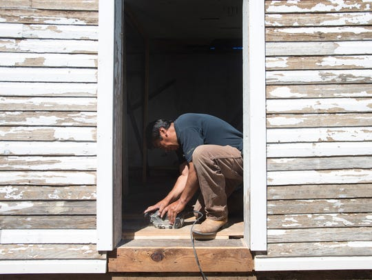 Raul Serrano sands floorboards in the James Ross proving-up house during restoration at The Farm in Lee Martinez Park on Friday. The home, built in 1891, is the last structure in Larimer County associated with the 1862 Homestead Act.