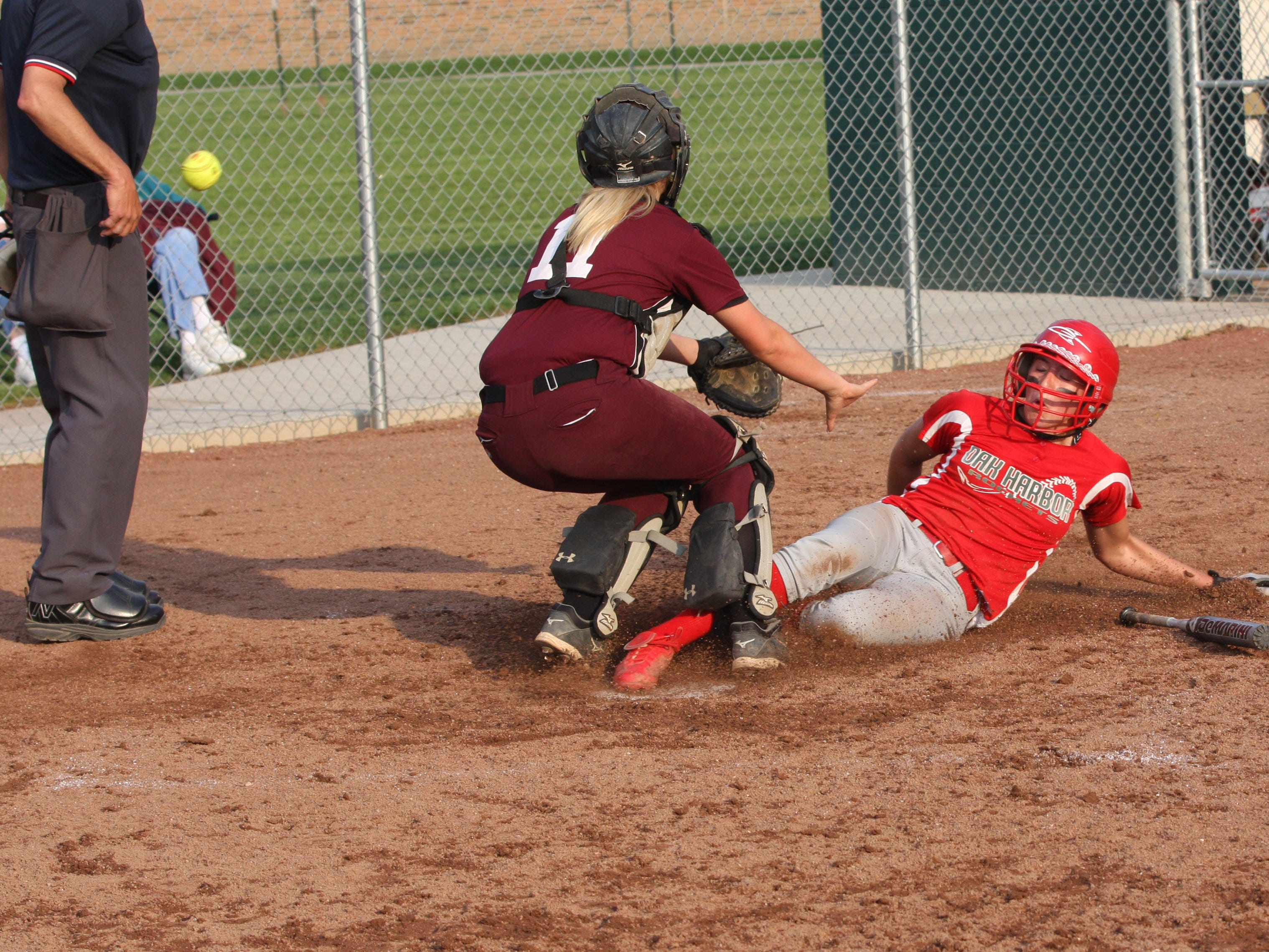 Oak Harbor's Ashley Riley scores the winning run Friday as the ball gets away from Willard's Callie Jones. The Rockets defeated Willard 2-1 in 12 innings in the sectional tournament at Oak Harbor.