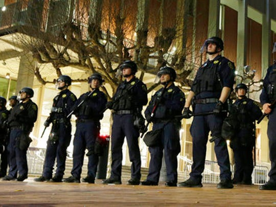 "FILE - In this Feb. 1, 2017 file photo, University of California, Berkeley police guard the building where Breitbart News editor Milo Yiannopoulos was to speak. The campus is bracing for a showdown next week, when the conservative provocateur Ann Coulter has vowed to speak in defiance of the university's wishes. Officials, police and the campus Republicans who invited Coulter, say there are valid concerns for violence in what is being called an ongoing ""Battle of Berkeley."""