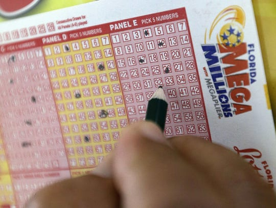 A customer fills out a Mega Millions ticket at a store