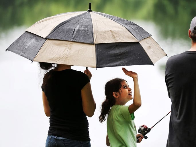 June 4, 2016 - Ava Lewellen, 9, bats at errant raindrops as her mom Ashlee King holds the umbrella during Lakeland's annual Children's Fishing Rodeo at IH Managerial Park Lake. Despite the rainy morning over 100 kids turned out to compete at the lake which was recently stocked with 800 pounds of catfish.
