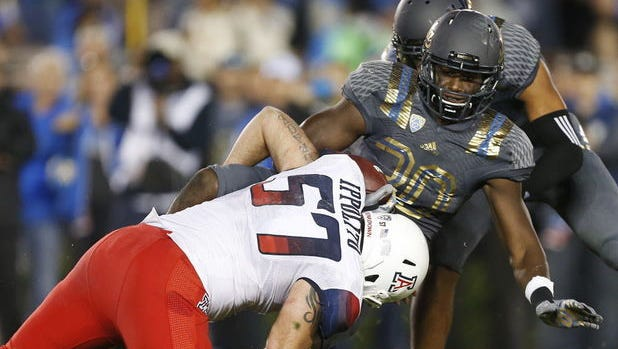 Arizona linebacker Cody Ippolito (57) stops UCLA running back Myles Jack (30) on third down in the red zone during the second quarter of the No.14 University of Arizona Wildcats vs. No. 25 UCLA Bruins college football game on Sat., Nov. 1, 2014, at the Rose Bowl in Pasadena, Calif.