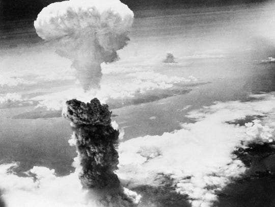 A giant column of smoke rises to form a mushroom cloud