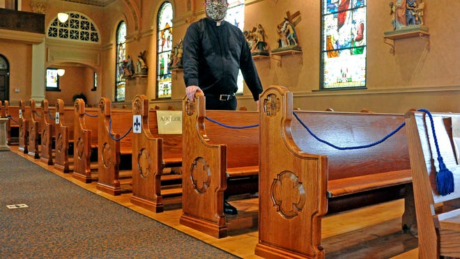 The Rev. Richard Samide of St. Mary of the Immaculate Conception Catholic Church in Wooster stands in an open pew. Every tthird pew is open with the rest roped off.