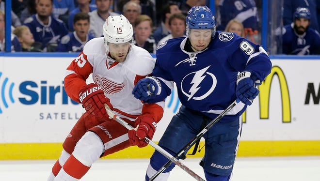 Detroit Red Wings center Riley Sheahan, left, and Tampa Bay Lightning center Tyler Johnson battle for a loose puck during Game 5 on Saturday, April 25, 2015, in Tampa.