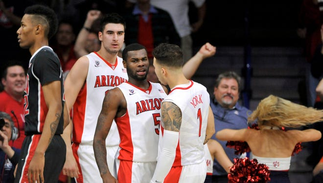 Arizona Wildcats guard Kadeem Allen (5) celebrates with center Dusan Ristic (14) (left) and guard Gabe York (1) during the first half against the UNLV Rebels at McKale Center.