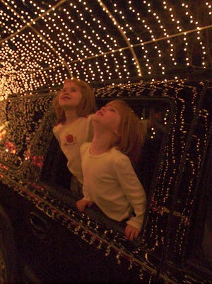 Kaitlyn Fleming and her sister Morgan Fleming, both of Yardley, Pa, admire tunnel of lights at Shady Brook Farm's drive-in holiday lights display in Yardley, Pa.