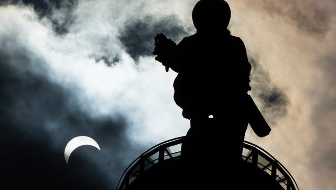 The statue of William Penn atop City Hall in Philadelphia is seen near the partial eclipse in August.