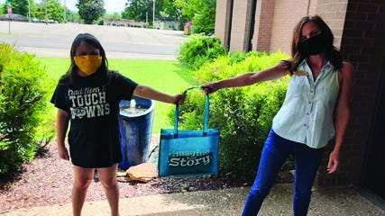 A summer reader accepts a bag from librarian Brittany Downs.