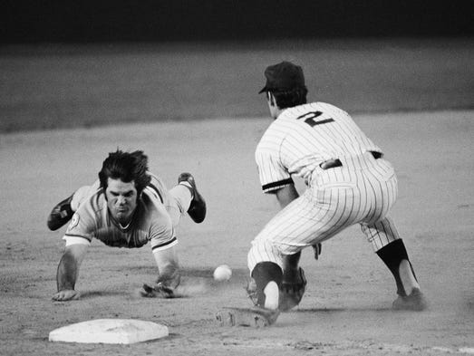 Pete Rose slides head first, feet in the air, as he