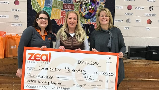 During a school assembly at Grandview Elementary to announce teacher Cynthia Gibson's award as hardest-working teacher, Principal Renee Valentine (right) accepts a check for $500 from Zeal Credit Union to be used by the school. Making the presentation is Tiffany Sweet (left), youth and community development coordinator for Zeal Credit Union.