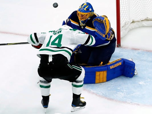 St. Louis Blues goalie Jake Allen, right, watches the puck after it bounced off Dallas Stars' Jamie Benn (14) during the second period of an NHL hockey game Thursday, Dec. 7, 2017, in St. Louis. (AP Photo/Jeff Roberson)