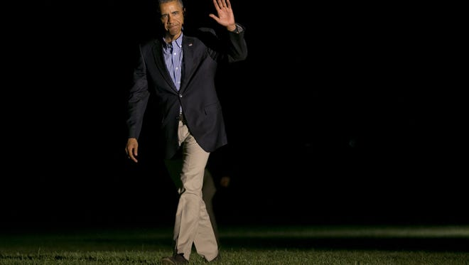 President Barack Obama waves as he returns to the White House in Washington, Sunday after a weekend in California where spoke at the Annual Meeting of the U.S. Conference of Mayors, attended DNC events, and later played golf.