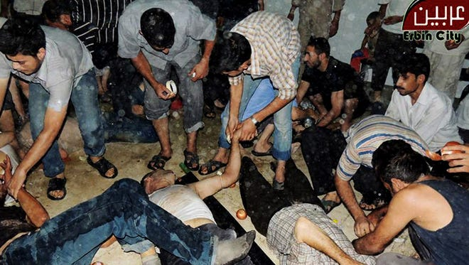 This citizen journalism image provided by the Local Committee of Arbeen, which has been authenticated based on its contents and other AP reporting, shows Syrian citizens receiving treatment after an alleged poisonous gas attack fired by regime forces, according to activists in Damascus, Syria, on Aug. 21.