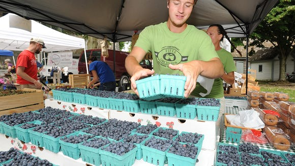 Kyle Brennan from Fifer Orchards puts fresh blueberries out for sale at the Lewes Farmers Market during the 2015 season.