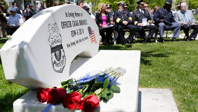 A rose for each of the four police officers killed in Fond du Lac in the line of duty were placed on a bench dedicated to Officer Craig Birkholz.