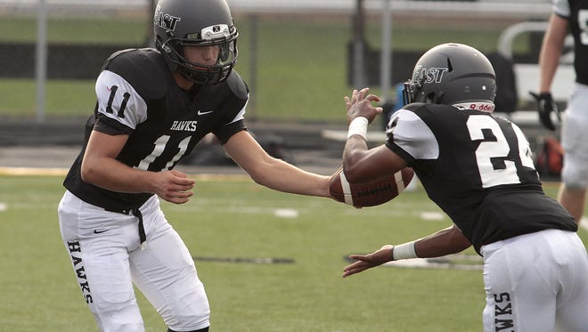 Quarterback Dylan Fry hands the ball off to Silas Ingram of Lakota East.  Loveland and Lakota East met on the turf as part of the Skyline Chili Crosstown Showdown.