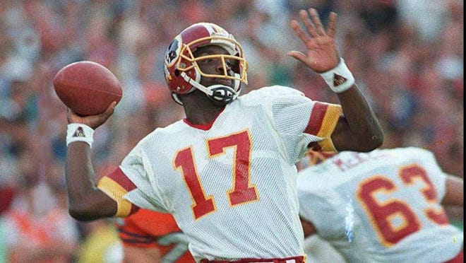 Washington Redskins quarterback Doug Williams is about to let go of a pass Jan. 31, 1988, during the first quarter of Super Bowl XXII with the Denver Broncos in San Diego.  Credit: AP/ELISE AMENDOLA