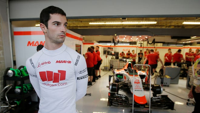 Alexander Rossi stands outside of his garage during a delay in the second practice session for the Formula One U.S. Grand Prix auto race at the Circuit of the Americas, Oct. 23, 2015, in Austin, Texas