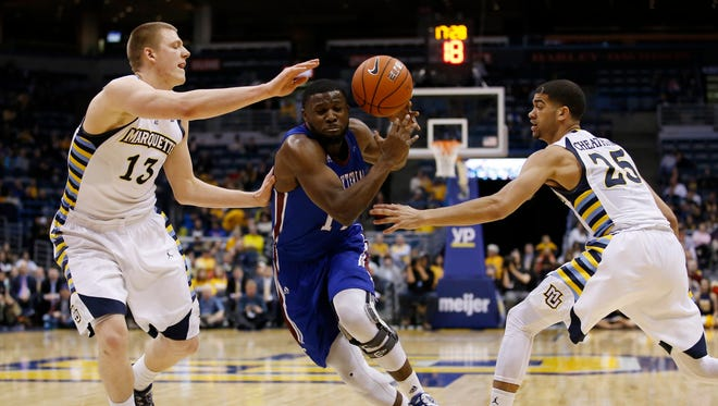 Presbyterian's Reggie Dillard loses the ball as he drives between Marquette's Henry Ellenson (13) and Haanif Cheatham (25) during the second half of an NCAA college basketball game on Sunday in Milwaukee.