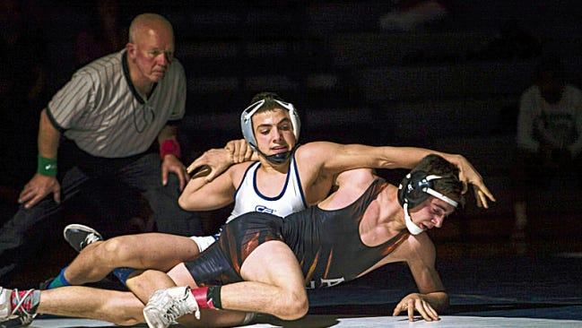 Piedra Vista's Nick Rino, top, and Aztec's Austin Littlefield wrestle for the District 1-5A title on Feb. 14 at Jerry A. Conner Fieldhouse in Farmington.