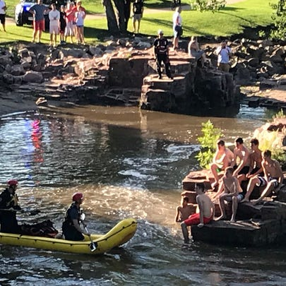 Firefighters use an inflatable boat to reach a group