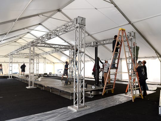 Crews build the runway and stage inside a tent for