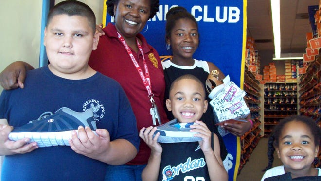 A member of the James O. Jessie Desert Highland Unity Center poses with students from the center who have just received back-to-school shoes, courtesy of the Kiwanis Club of Palm Springs