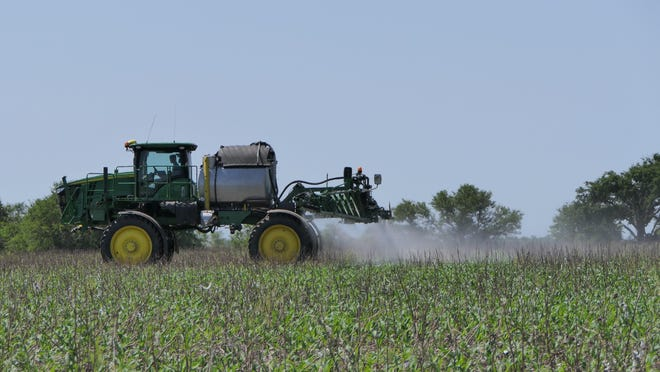 Cody Oden, 16, sprays the family corn fields at Sterling Heritage Farms in Sterlingc.