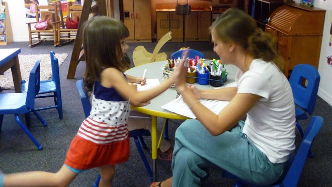 Evelynn Aguirre McClure, left, gives her teacher Brittany Polanco a high five after working with her. This is Evelynn's first experience in preschool. She attends the New Mexico PreK program at Alpha School.