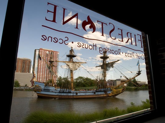 The Kalmar Nyckel is reflected in the window of the FireStone Roasting House on the Wilmington Riverfront.