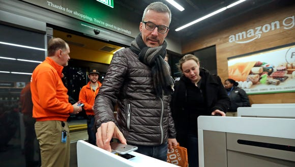 A customer scans his Amazon Go cellphone app at the