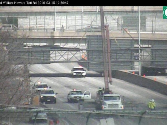Crews work to remove a sign truss that was damaged by construction equipment.