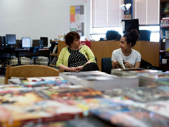 Millville librarian Kathleen Galarza, left, reads with