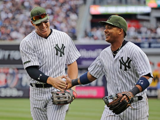 New York Yankees' Aaron Judge, left, and Starlin Castro, right, celebrate after Judge caught a ball hit by Oakland Athletics' Trevor Plouffe after Castro lost control of the ball during the sixth inning of a baseball game Saturday, May 27, 2017, in New York.