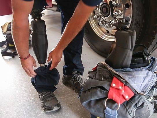Lt. Brandon Anderson shows how he detaches his prosthetic