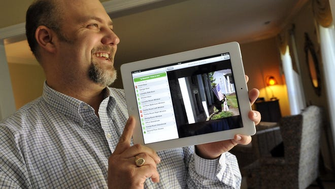 In this file photo, Comcast's Frank Purcell demonstrates how his company's Xfinity Home service can show live video feeds from security cameras placed around the house on consumer devices such as the iPad in Annapolis, Md., on May 18, 2012.