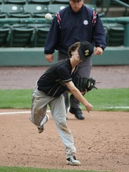 Rush-Henrietta third baseman Lukas Haefner loses his hat after making a hard throw to first to throw out McQuaid's Noah Campanelli during the Section V Class AA championship game.
