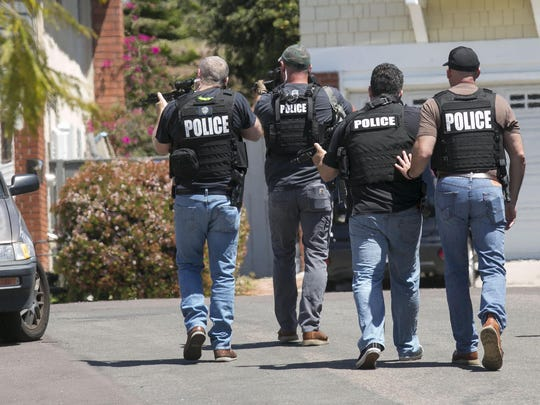 Heavily-armed San Diego police officers approach a house thought to be the home of 19 year-old John T. Earnest, who is a suspect in the shooting of four people in a Poway, Calif., synagogue, killing one, on Saturday, April 27, 2019, in San Diego. (John Gibbins/San Diego Union-Tribune/TNS)