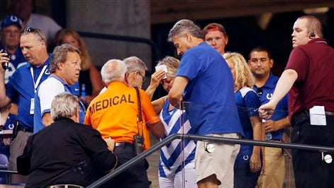 A fan is helped by emergency workers at Lucas Oil Stadium in Indianapolis on Thursday, Sept. 3, 2015, after she was injured by a falling bolt as the roof was being opened just before halftime of the preseason game between the Indianapolis Colts and the Cincinnati Bengals. Two other fans also sustained injuries.