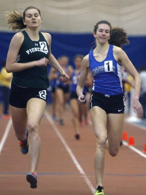 Jillian Turner of New Providence (left) and Rachel Suss of Metuchen compete in the 1600 during the Central Groups I and IV indoor track sectional championships at the Bennett Center in Toms River on Friday.